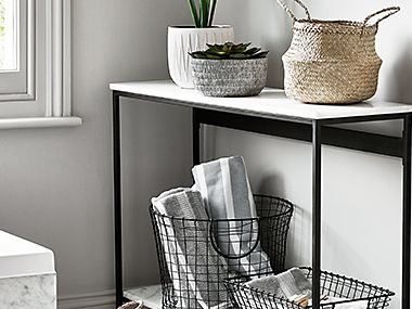 Console table with plants and wire baskets