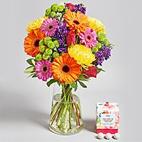 Bright flower arrangement with chocolates