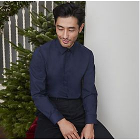 Model next to Christmas tree wearing navy shirt and black trousers
