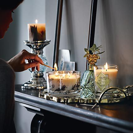 Scented candles and ornaments on a mantelpiece