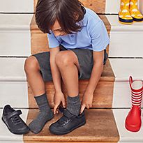 Boy sitting on stairs putting on scuff resistant leather shoes