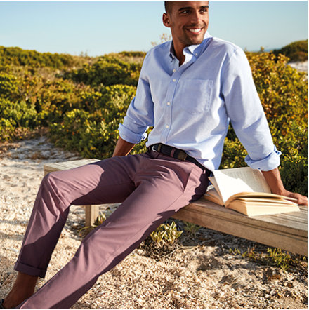 Man sitting on a bench wearing purple chinos and casual shirt