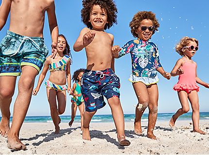 A group of children wearing swimwear on a beach