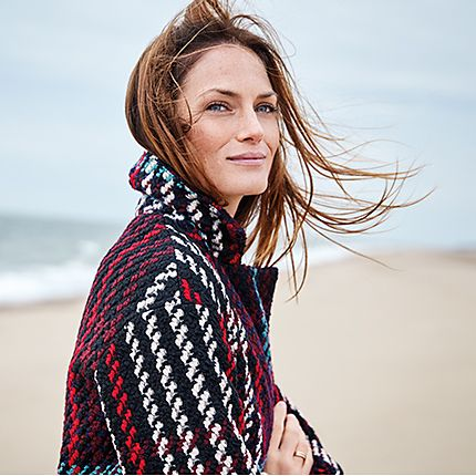 Woman on the beach wearing a checked wool coat