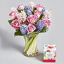 Roses and hyacinths in vase with box of chocolates