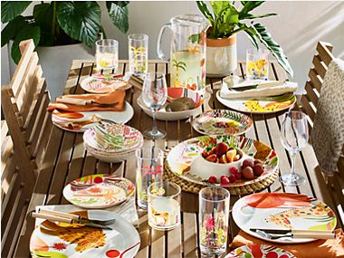 A garden table set with colourful picnicware