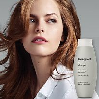 Woman with bouncy long hair next to a bottle of Living Proof Shampoo