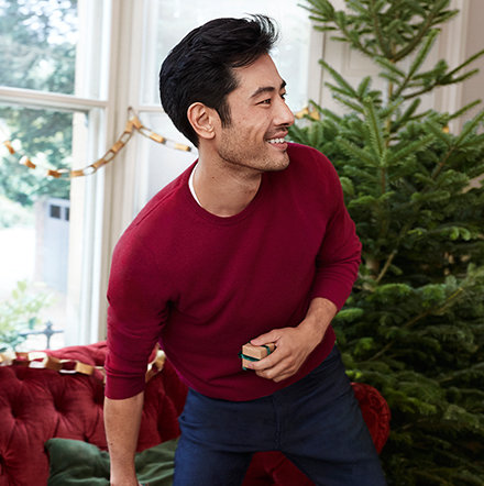 Man wearing cashmere red jumper standing in front of a Christmas tree