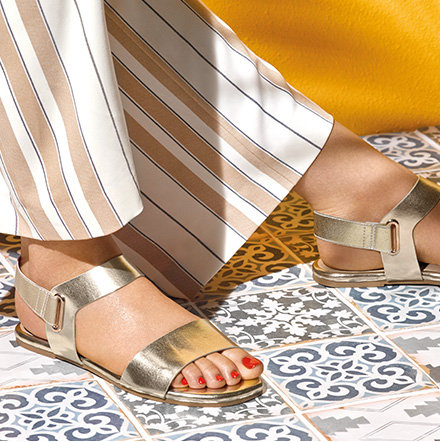 Woman stood on a tiled floor wearing striped trousers and gold sandals