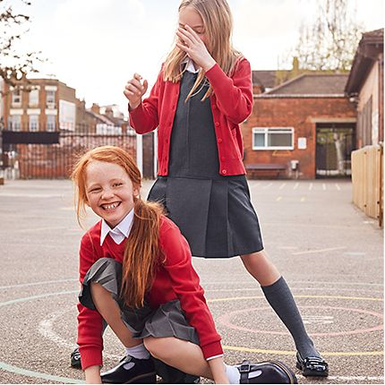 Two girls in playground wearing school uniform