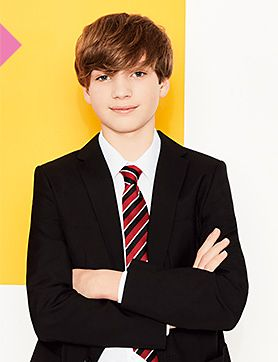 A boy wearing a blazer, white shirt and a school tie