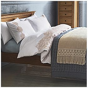 Patterned bedding set and bedcover on wooden bed