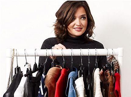 Woman standing behind a rail of clothing