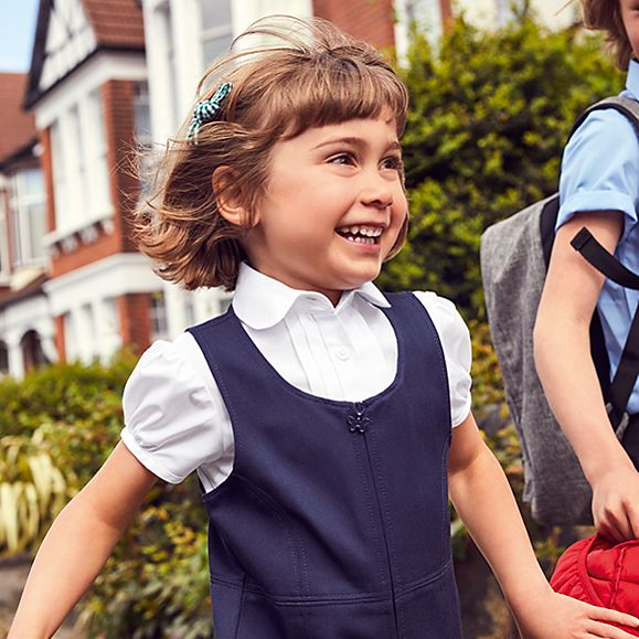 Girl wearing an M&S short-sleeved school shirt and grey school pinafore