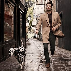 Man wearing winter coat walking a dog