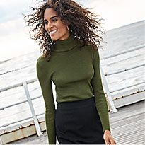 Woman on pier wearing a green roll-neck jumper and black midi skirt