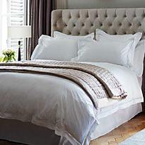 Divan bed with white bed linen and pink cover