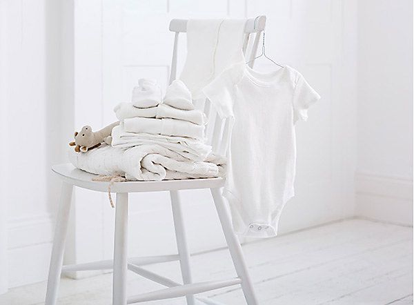 White chair with baby blankets and soft baby toys
