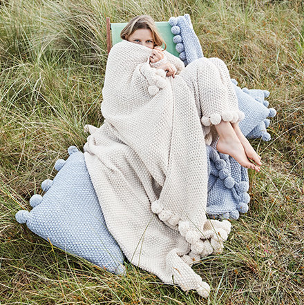 Woman with cosy blankets and cushions