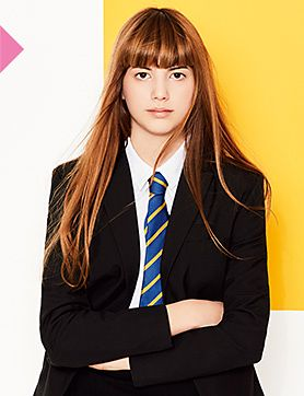 A girl wearing a black blazer with a white shirt and a school tie