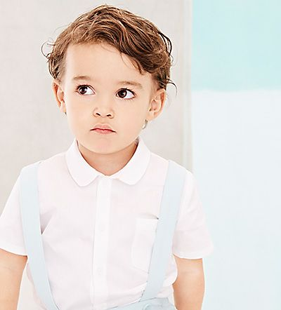 Boy wearing short sleeved cotton shirt with pale blue shorts and blue braces