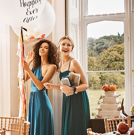 A close up of a wedding cake and two bridesmaids carrying a 'Happily Ever After' balloon