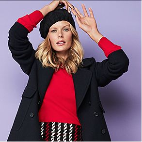 Model wearing black beret, black coat, red jumper and checked skirt