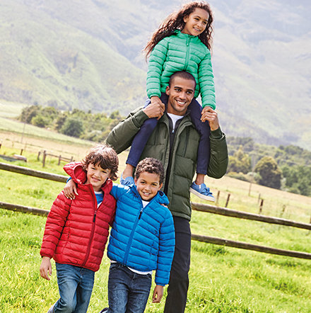 Man and three children in puffa coats outside in the countryside