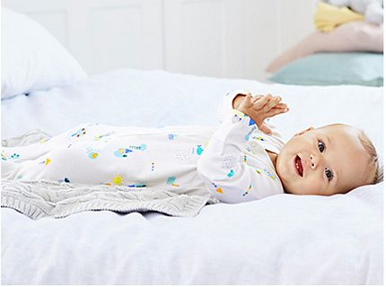 Baby lying on beg wearing M&S sleepwear
