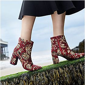 Woman wearing red and gold embroidered boots walking up a hill