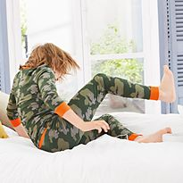 Boy tumbling on bed in camo M&S pyjamas