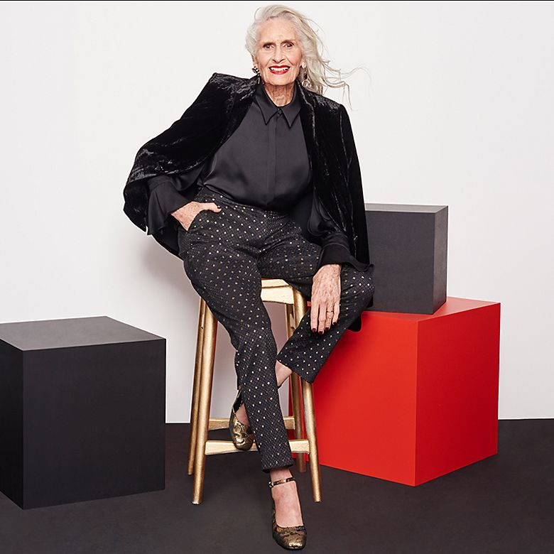 Model Daphne Selfe wears black velvet blazer, satin shirt, jacquard trousers and heels