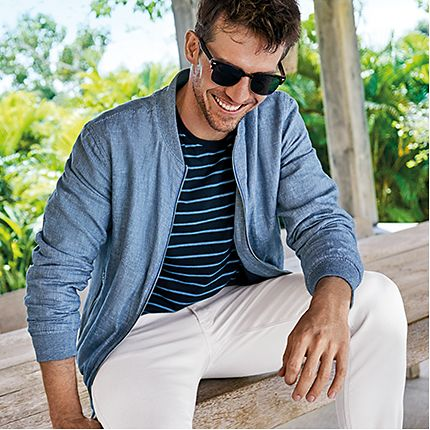 Man wearing white casual trousers, striped T-shirt and blue jacket