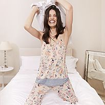 Woman on a bed wearing pyjamas