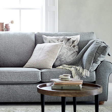 Grey sofa with cushions and throw in living room