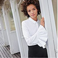 Woman on pier wearing a while frilled-sleeve shirt and black trousers