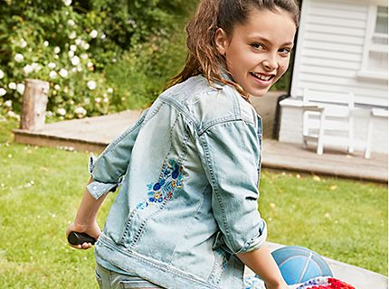Girl wearing faded denim jacket