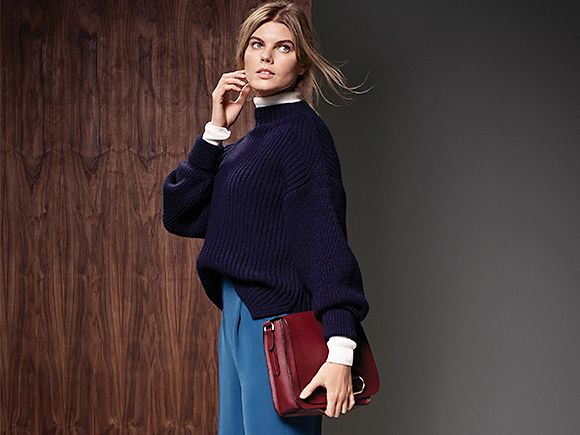 Model wears navy jumper, blue trousers and red bag