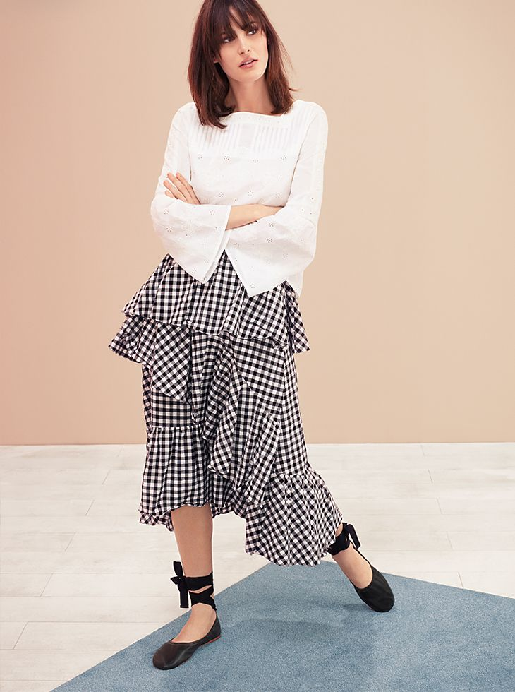 Woman wearing white top and ruffle gingham skirt