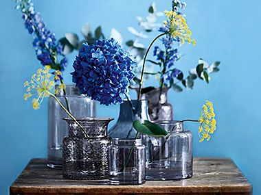 Flowers in vases on a wooden dresser