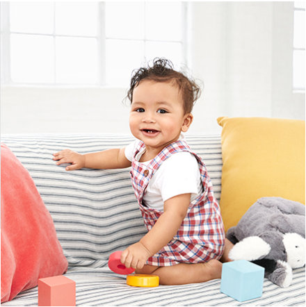 Baby playing with building blocks wearing a white bodysuit and checked dungarees