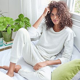 Woman relaxing on a bed wearing cream pyjamas
