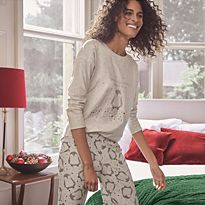 Woman getting ready for bed wearing Christmas pyjamas