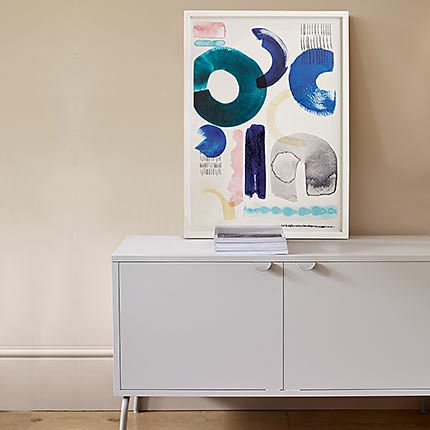 White sideboard with books and abstract wall art
