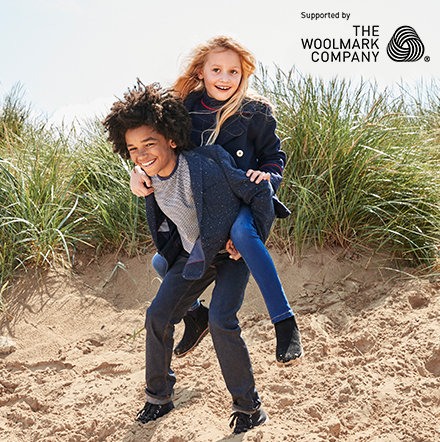 Boy giving a girl a piggyback wearing M&S winter coats and knitwear