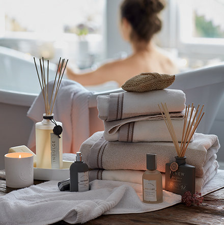Model in bath with towels, reed diffuser