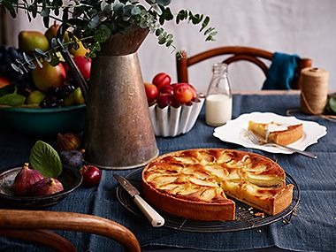 Table laid with bowls of fruit and an apple tart