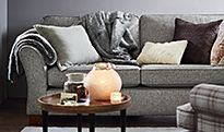 A grey sofa with a cream throw and cushions