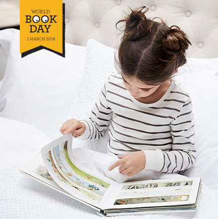 Girl reading a book to celebrate World Book Day