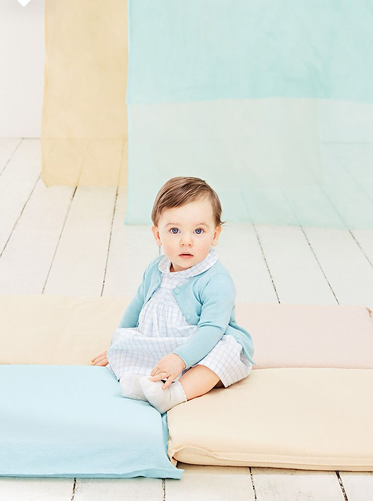 Baby girl in pale blue merino cardigan and dress